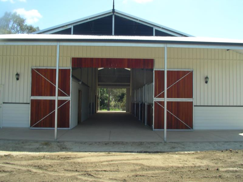 Double front wood doors at front of Breeze-Way Stable