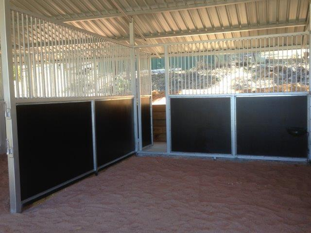 Stalls lined with black form ply large feed door access to back